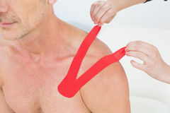 Hands putting on red kinesio tape on patients shoulder Stock Image