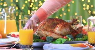 Hands putting roasted turkey on festive table closeup stock footage