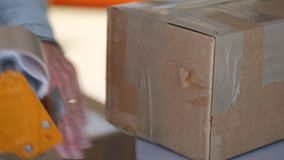 Hands putting self-adhesive tape on box. Hands putting self-adhesive tape with dispenser on brown cardboard box stock video