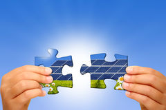 Hands and puzzle in backlight. Hands holding two jigsaw puzzle showing a green lawn and photovoltaic panels Stock Image