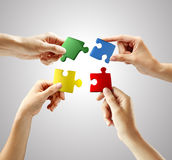 Hands and puzzle on gray background Royalty Free Stock Images