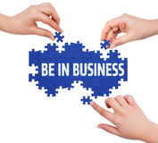 Hands with puzzle making BE IN BUSINESS word Royalty Free Stock Images