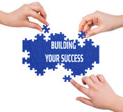 Hands with puzzle making BUILDING YOUR SUCCESS word  isolated on Royalty Free Stock Photos