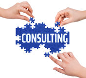 Hands with puzzle making CONSULTING word Stock Images