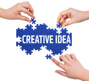 Hands with puzzle making CREATIVE IDEA word Stock Photo