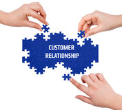 Hands with puzzle making CUSTOMER RELATIONSHIP word Royalty Free Stock Photos