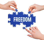Hands with puzzle making FREEDOM word Stock Photo