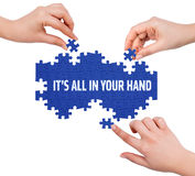 Hands with puzzle making IT'S ALL IN YOUR HAND word Royalty Free Stock Images