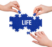 Hands with puzzle making LIFE word Royalty Free Stock Photos