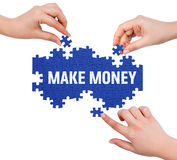 Hands with puzzle making MAKE MONEY word Stock Images