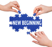 Hands with puzzle making NEW BEGINNING word Stock Image