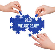 Hands with puzzle making 2019 WE ARE READY word Stock Image