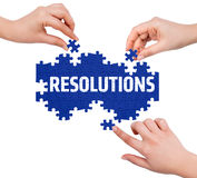 Hands with puzzle making RESOLUTIONS word Stock Photos