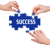 Hands with puzzle making SUCCESS word Royalty Free Stock Photo