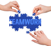 Hands with puzzle making TEAMWORK word Stock Images