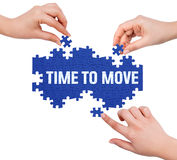 Hands with puzzle making TIME TO MOVE word Stock Photography
