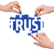 Hands with puzzle making TRUST word Royalty Free Stock Photos