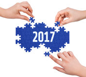 Hands with puzzle making 2017 word Stock Images