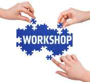 Hands with puzzle making WORKSHOP word Stock Photo