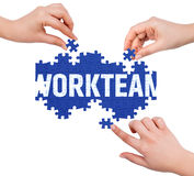 Hands with puzzle making WORKTEAM word Royalty Free Stock Images