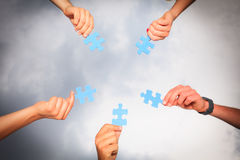 Hands With Puzzle Pieces. Against cloudy sky Stock Images