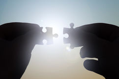Hands with puzzles circuit in the sun stock images