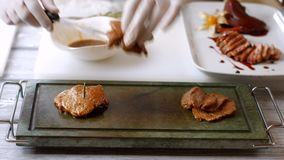 Hands quickly put meat. Cooked meat on dark tray. Chef prepared veal medallions. High-calorie dish for gourmets stock video