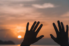 Hands raised against sunset sky. At sunset Royalty Free Stock Image