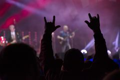 Hands raised by the crowd at live rock concert. Happy fans background. Audience hands and lights at concert stock photos