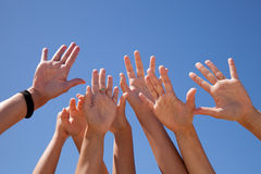 Hands raised to the sky. Many hands raised to the blue sky (some motion blur Royalty Free Stock Image