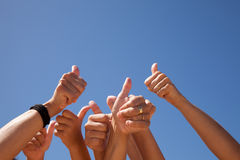 Hands raised to the sky. Many hands raised to the blue sky (some motion blur Stock Photography