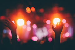 Hands raised up on a concert. Hands raised up on a night club concert with the colorful stage lights bokeh background Royalty Free Stock Photos