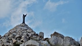 Hands raised veiled elk. Monuments, sky, architecture, sculptures, rocks, cross, travel, stone, mountain, ancient, nature, religion, blue, landscape, ruins Stock Photo