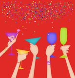 Hands of Women Raising Glasses in a Toast on Red. Hands raising glasses in a celebratory toast with confetti on a red background Royalty Free Stock Image