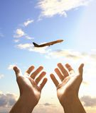 Hands reach for airplane Stock Photo