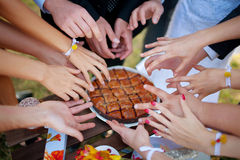 Hands reach for the cake. A lot of hands reaching for the cake Stock Photo