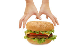 Hands reach for a hamburger Stock Photo