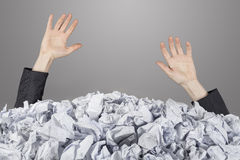 Hands reach out from big heap of crumpled papers. Hands reach out from heap of crumpled papers on gray background Stock Images