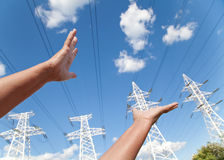 Hands reach for power transmission lines against blue sky Royalty Free Stock Photo