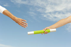 Hands reaching baton for teamwork Stock Photos