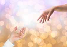 Hands reaching for eachother helping with sparkling light bokeh background Royalty Free Stock Photos