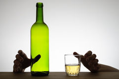 Hands reaching for a glass and a bottle Royalty Free Stock Photography