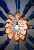 Hands reaching for light bulb. Many hands reaching for one light bulb from all directions stock photos