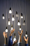 Hands reaching for light bulbs stock photo