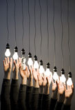 Hands reaching for light bulbs stock image
