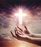 Hands reaching out with crucifix cross in sunset sky Stock Images