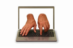 Hands reaching out of laptop display and typing. Composite picture - hands reaching out of laptop display and typing