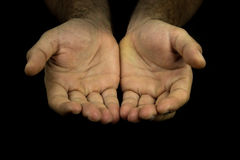 Hands reaching out towards camera. On dark background