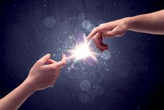 Hands reaching to light a spark. Two male hands reaching towards each other, almost touching with fingers, lighting spark in galaxy background concept Stock Image