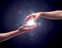 Hands reaching to light a spark. Two male hands reaching towards each other, almost touching with fingers, lighting spark in galaxy background concept Stock Photography
